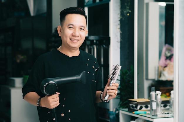 Alegre peluquero masculino asiático posando con secador de pelo y cepillo en el salón