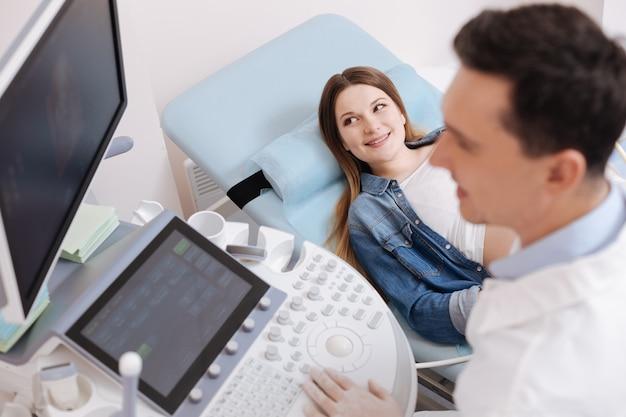 Alegre practicante calificado que trabaja en la clínica mientras realiza una exploración del vientre de embarazada con ultrasonido y expresa alegría