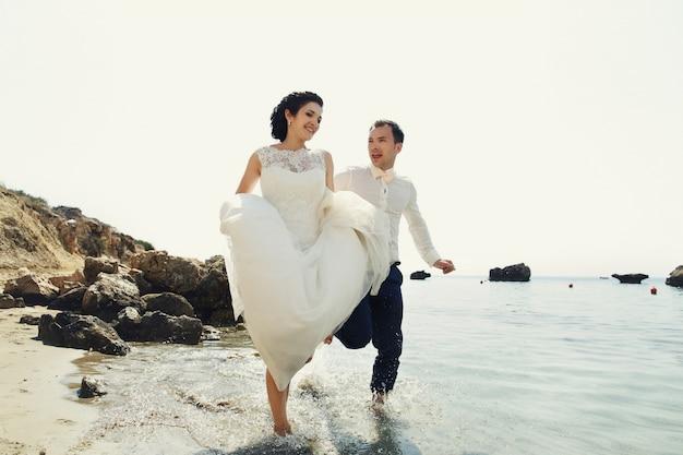 Alegre recién casados correr a lo largo de la playa