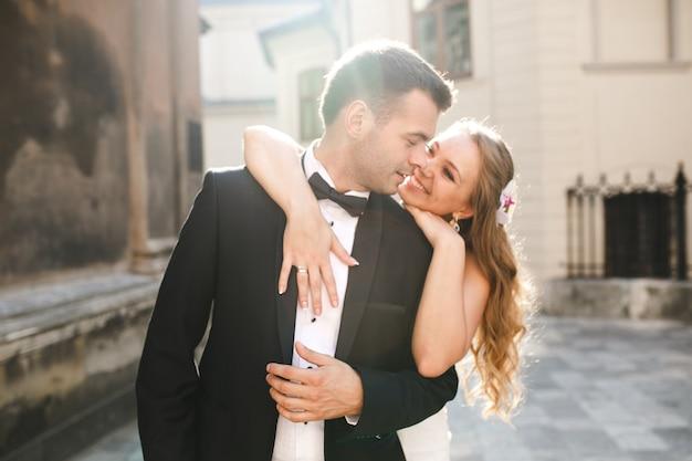 Alegre recién casados en la luz del sol en la calle