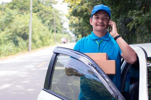 Alegre repartidor asiático sosteniendo una caja y sonriendo mientras está de pie en la carretera