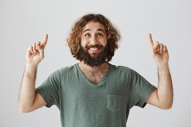 Alegre sonriente chico del medio oriente con barba mirando y apuntando con el dedo hacia arriba