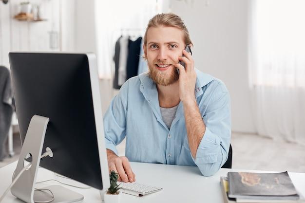 Alegre sonriente estudiante barbudo recibe la llamada de un amigo, se sienta en una oficina ligera, se viste con una camisa azul, termina el trabajo pronto. independiente masculino guapo tiene conversación telefónica, discute ideas.
