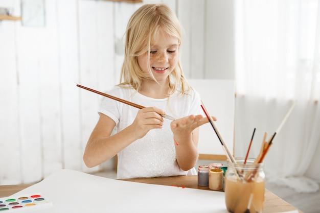 Alegre, sonriente y feliz niña rubia en camiseta blanca dibujando algo en su palma con un pincel.