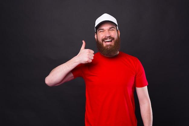 Alegre, sonriente, joven, en, camiseta roja, actuación, pulgar, arriba, negro