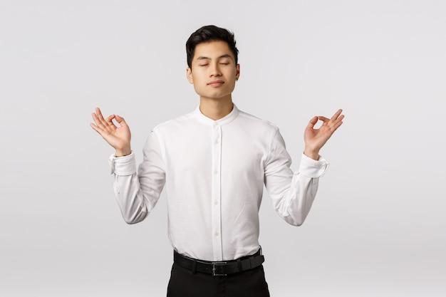 Alegre sonriente joven empresario asiático con camisa blanca aliviada