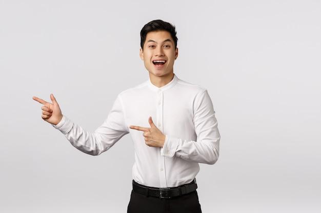Alegre sonriente joven empresario asiático con camisa blanca apuntando hacia el lado