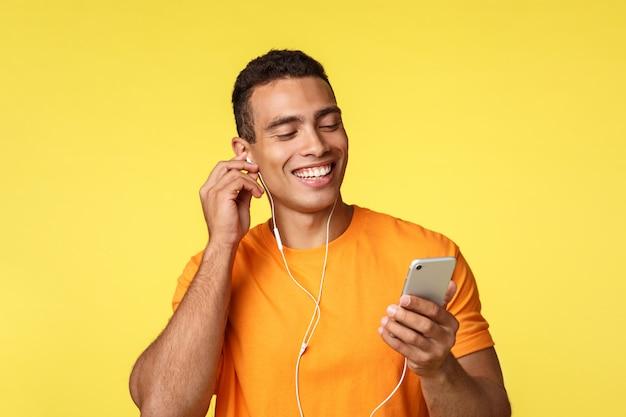 Alegre sonriente joven masculino en camiseta naranja, con smartphone
