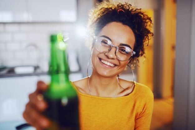 Alegre sonriente linda morena caucásica bronceada con cabello rizado sentado en la fiesta y brindando con cerveza.