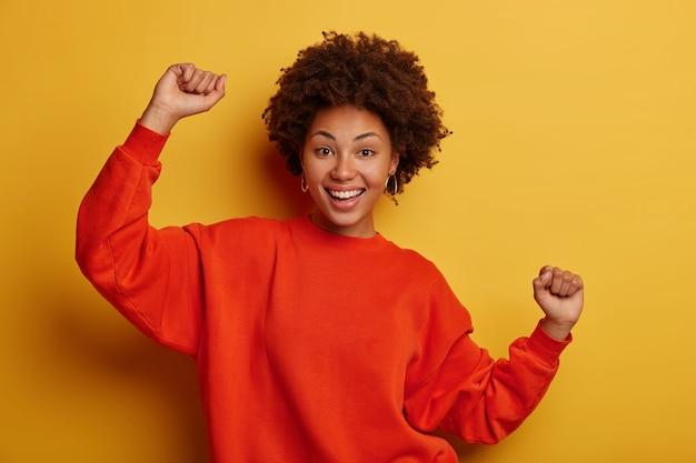 Alegre sonriente mujer afroamericana se divierte, expresa felicidad, aprieta los puños, disfruta de la fiesta con amigos