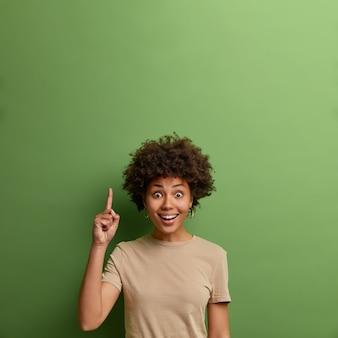 Alegre sorprendida mujer adulta de pelo rizado apunta al espacio de copia en blanco para texto comercial, demuestra presentación de ideas, promoción impresionante hacia arriba, vestida con camiseta beige informal, pared verde