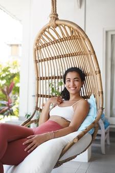 Alegre tierna mujer feliz con cabello oscuro y rizado disfrutando de unas vacaciones sentado en una silla de ratán