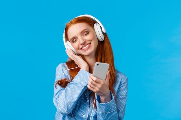 Alegre tierna mujer pelirroja en pijama, inclinando la cabeza disfrutando escuchando música