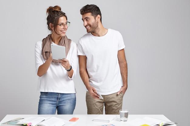 Alegre trabajadora creativa positiva revela algo para que su colega usa tableta