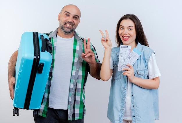 Alegre viajero adulto pareja hombre sosteniendo maleta y mujer sosteniendo boletos de viaje haciendo el signo de la paz y mirando