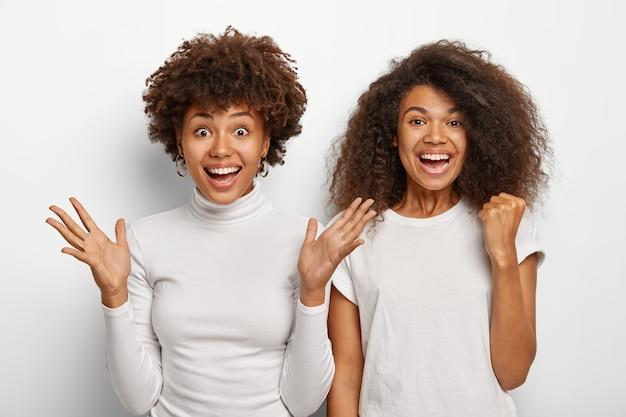 Alegres y afortunadas dos mujeres se divierten, gesticulan activamente con las palmas de las manos, cierran el puño, disfrutan de noticias increíbles, obtienen una buena relevación, se visten con ropa informal, aisladas sobre fondo blanco.