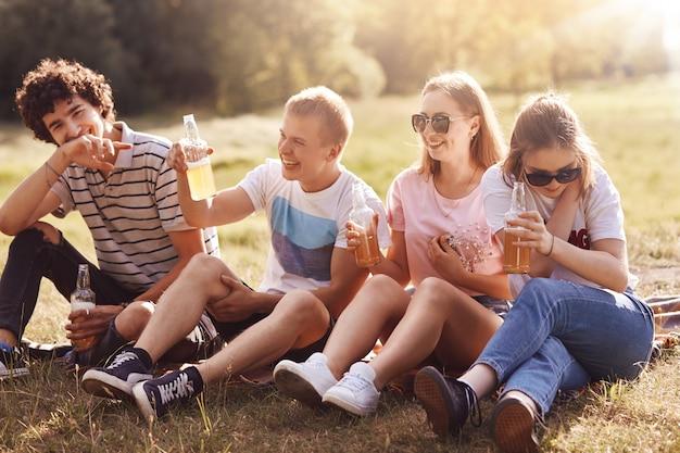 Los alegres y alegres amigos se alegran y pasan el día de verano al aire libre, sonríen alegremente, beben sidra fría o limonada, las niñas visten sombras, se ríen de la broma divertida del compañero masculino. concepto de estilo de vida