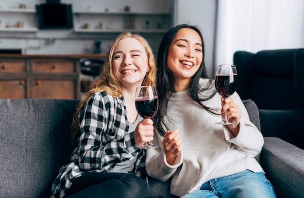 Alegres amigos bebiendo vino