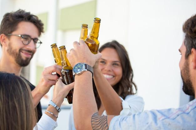 Alegres amigos brindando cerveza y celebrando el éxito
