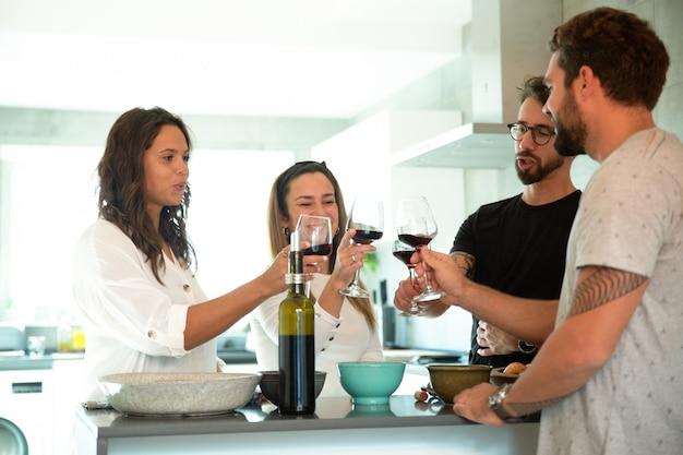 Alegres amigos brindando vino en la cocina