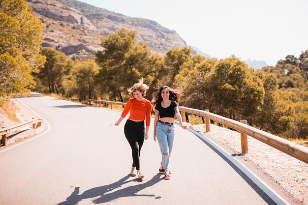 Alegres amigos caminando por la carretera de campo
