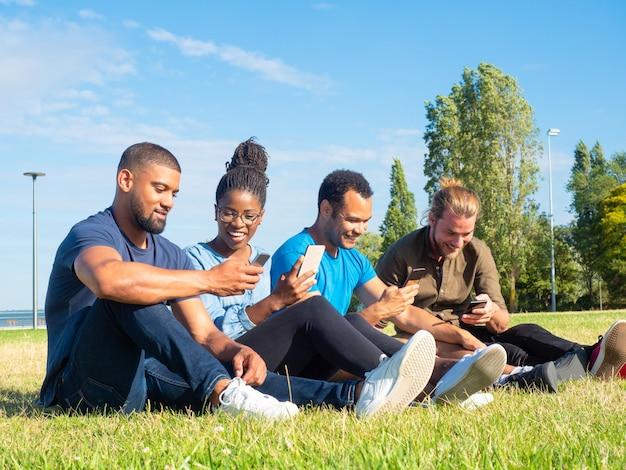 Alegres amigos multiétnicos que usan teléfonos inteligentes en el parque