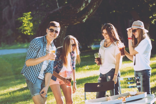 Alegres amigos de picnic en el parque. comiendo pizza