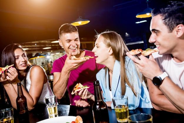 Alegres amigos en el pub. beber cerveza, comer pizza, hablar, divertirse.