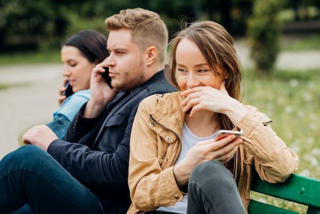 Alegres amigos relajarse en el banco en el parque