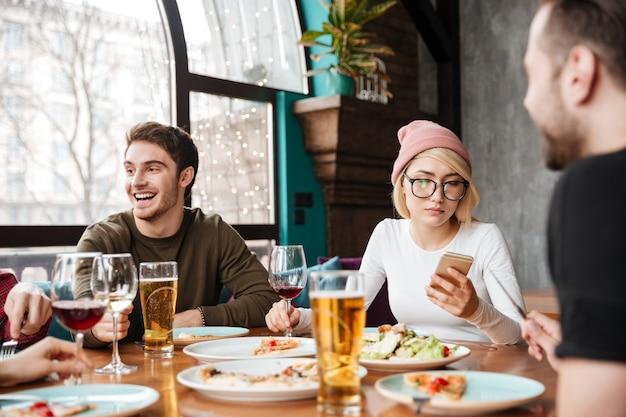 Alegres amigos sentados en la cafetería comiendo y bebiendo alcohol.