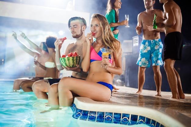 Alegres amigos sonriendo, regocijándose, descansando en la fiesta junto a la piscina