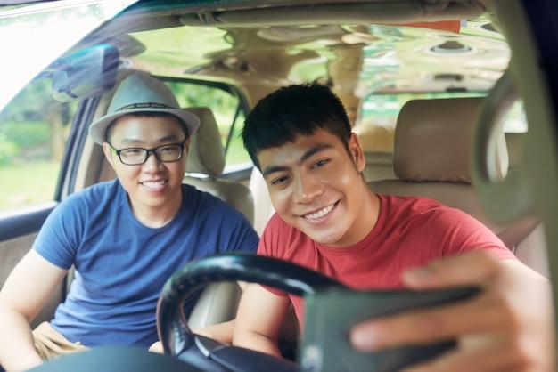 Alegres amigos varones asiáticos sentados juntos en el coche y tomando selfie