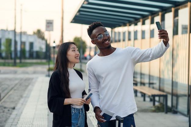 Alegres amigos varones y mujeres multirraciales haciendo selfie en smartphone con pasaportes y boletos antes del viaje.