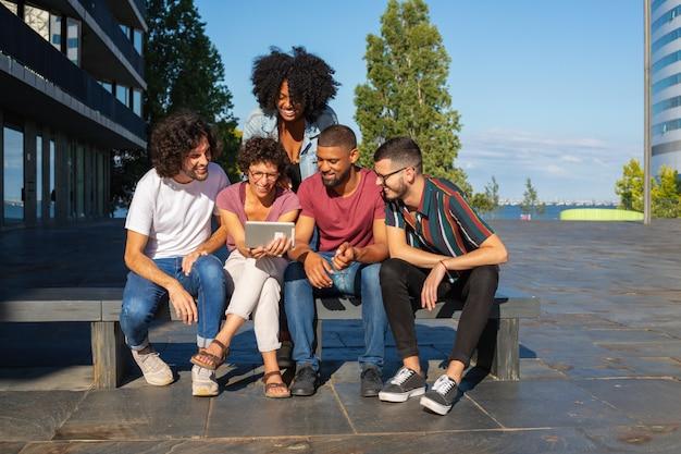 Alegres amigos viendo videos en tableta al aire libre