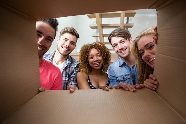 Alegres amigos vistos a través de una caja de cartón