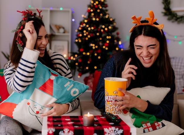 Alegres chicas guapas con corona de acebo y diadema de renos comen palomitas de maíz y juegan sentados en sillones y disfrutando de la navidad en casa