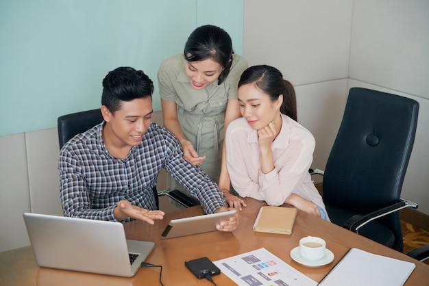 Alegres colegas asiáticos sentados y de pie alrededor del escritorio y mirando la tableta juntos
