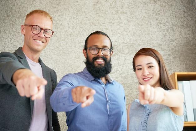 Alegres colegas multiétnicos de pie en la oficina y apuntando hacia la cámara