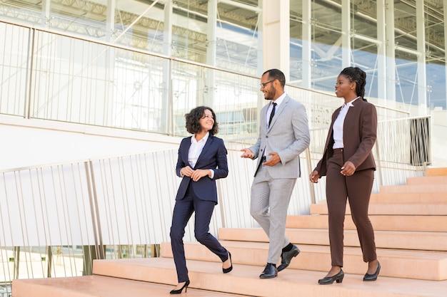 Alegres colegas de negocios caminando en el edificio de oficinas