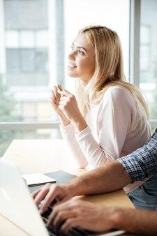 Alegres dos colegas en el coworking de oficina mientras usan laptop