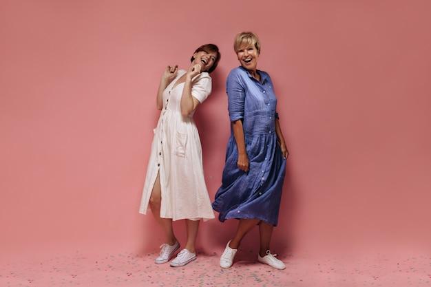 Alegres dos mujeres frescas con peinado corto en vestidos de verano midi y zapatillas blancas riendo sobre fondo rosa aislado.