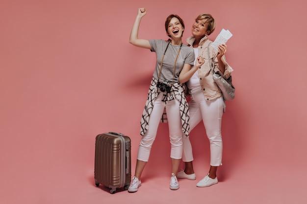 Alegres dos mujeres con el pelo corto en pantalones blancos delgados y zapatillas de deporte sonriendo y posando con maleta, cámara, boletos y bolso sobre fondo aislado.