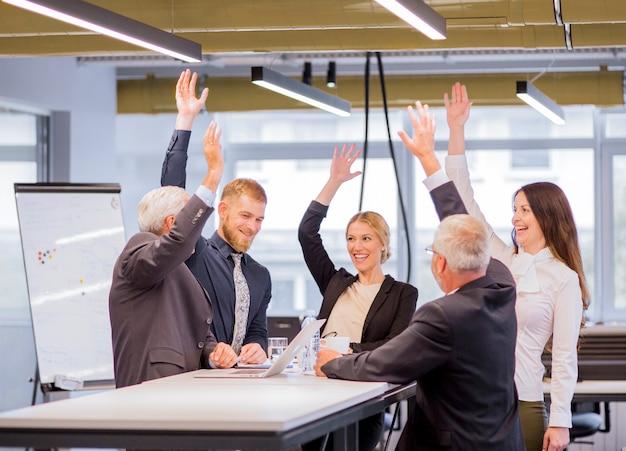 Alegres empresarios en la reunión levantando los brazos.