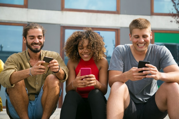 Alegres estudiantes multiétnicos enfocados que usan sus teléfonos
