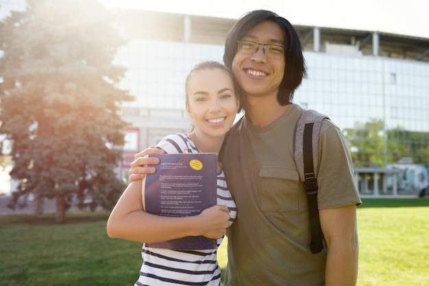 Alegres estudiantes de pie al aire libre