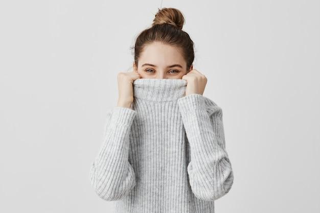 Alegres expresiones faciales de mujer mirando desde el cuello de su suéter con ojos felices. mujer contenta con cabello castaño atado engañando escondiendo su rostro en la ropa. concepto de diversión y alegría