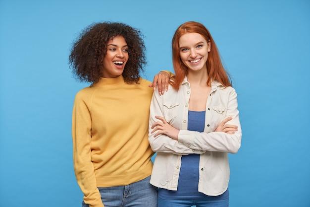 Alegres hermosas mujeres jóvenes riendo alegremente mientras posan sobre la pared azul, estando en alto espíritu mientras pasan un buen rato juntos