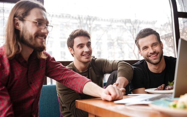 Alegres hombres amigos sentados en la cafetería mientras se come. usando una computadora portátil.