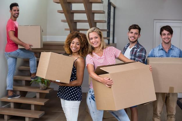 Alegres jóvenes amigos llevando cartón en casa nueva
