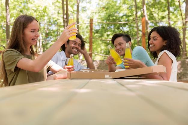 Alegres jóvenes amigos multiétnicos estudiantes afuera bebiendo jugo comiendo pizza